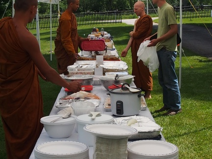 Ajahn Sek, and Vens. Atulo and Sallekho receive food
