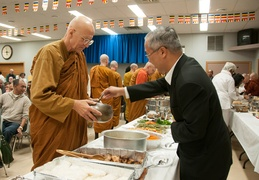 Luang Por Viradhammo accepts alms from ambassador Pisan