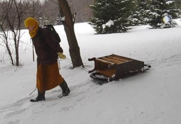 Bhante Khemaratana moves some furniture on a sled