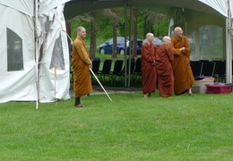 Monastics wait by the tent as guests as the guests start to arrive for Vesak